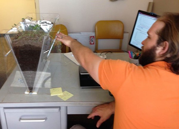 Tony Perlinski, Chadron State College associate professor of applied sciences, uses a clear-sided demonstration box to show how infiltration rates differ in soil with plant cover compared to bare earth. The experiment is part of a hydrology class offered in the spring of 2016. (Photo by George Ledbetter)